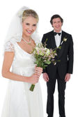 Bride holding bouquet with groom in background — Stock Photo