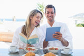 Couple with book and digital tablet on breakfast table — Stockfoto