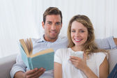 Relaxed couple reading book on couch — Stock Photo