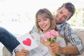 Couple with flowers and greeting card at home — Stock Photo