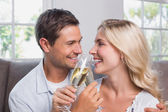 Cheerful loving couple with champagne flutes at home — Stock Photo