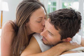 Young woman kissing man in bed — Stock Photo