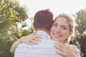 Smiling young couple embracing in park — Stock Photo