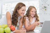 Mother and daughter using laptop in kitchen — Stock Photo