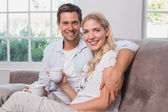 Relaxed loving couple with coffee cups sitting on sofa — Stock Photo
