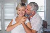 Mature man kissing a happy woman — Stock Photo