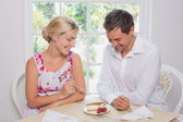 Happy young couple with pastry at dining table — Stock Photo