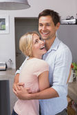 Happy young couple embracing in the kitchen — Stock Photo