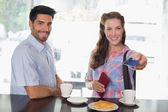 Couple with woman holding out credit card at coffee shop — Stock fotografie