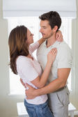 Loving man embracing woman at home — Stock fotografie