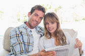 Loving happy couple reading newspaper on couch — Stock Photo