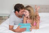 Smiling young couple with gift box in bed — Stock Photo