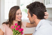 Happy young couple with flowers at home — Stock Photo