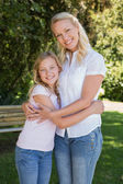 Mother and daughter embracing in park — Stock Photo