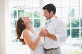 Loving young couple dancing at home — Stock Photo