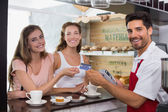Friends with woman holding out credit card at coffee shop — Stockfoto