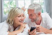 Cheerful mature couple reading text message at home — Stock Photo