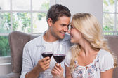 Loving young couple with wine glasses at home — Stock Photo