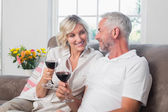 Happy loving mature couple with wine glasses in living room — Stock Photo