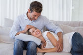 Happy woman resting on mans lap on couch — Stock Photo