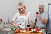 Mature man with wine glass and woman chopping vegetables in kitchen — 图库照片