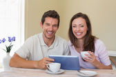 Happy couple using digital tablet while having coffee — Stockfoto