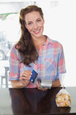 Smiling woman holding credit card at coffee shop counter — Stock Photo