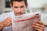 Concentrated young man reading newspaper — Stock Photo