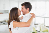 Loving young couple embracing in kitchen — Stock Photo