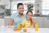 Mother and daughter sitting at breakfast table — Stock Photo
