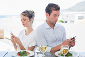 Couple text messaging at food table — Stock Photo