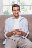 Casual man reading text message on sofa — Stock Photo