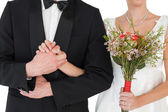 Mid section of bride and groom holding hands — Stock Photo