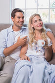 Relaxed couple with coffee cups in living room at home — Stock Photo