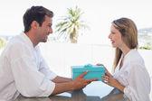 Man giving woman gift box at home — Stock Photo