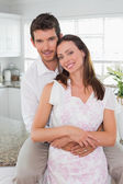 Loving man embracing woman from behind in kitchen — Stock Photo