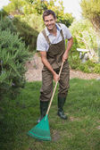 Young man in dungarees raking the garden — Stock Photo
