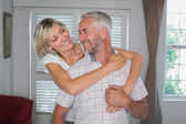 Woman embracing mature man from behind at home — Stock Photo
