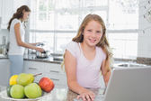 Daughter using laptop with mother cooking food in background at the kitchen — Stock Photo