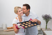 Man kissing woman's cheek as she holds freshly baked cookies in — Stock Photo