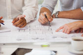 Mid section of business people working on blueprints — Stock Photo