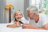 Cheerful mature couple reading text message — Photo