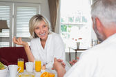 Cheerful woman having breakfast with cropped man — Photo