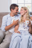 Relaxed loving young couple with coffee cups in living room — Stock Photo