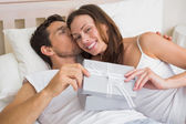 Relaxed couple with gift box lying together in bed — Stock Photo