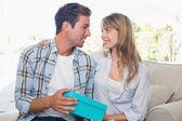 Loving couple with gift box sitting on sofa — Stock Photo