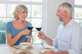 Happy mature couple toasting wine glasses over food — Stockfoto