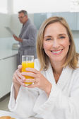 Smiling woman holding orange juice with man in background — Stock Photo