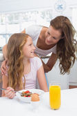 Mother looking at daughter while having breakfast in kitchen — Stock Photo