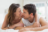 Relaxed young couple lying in bed — Stock Photo